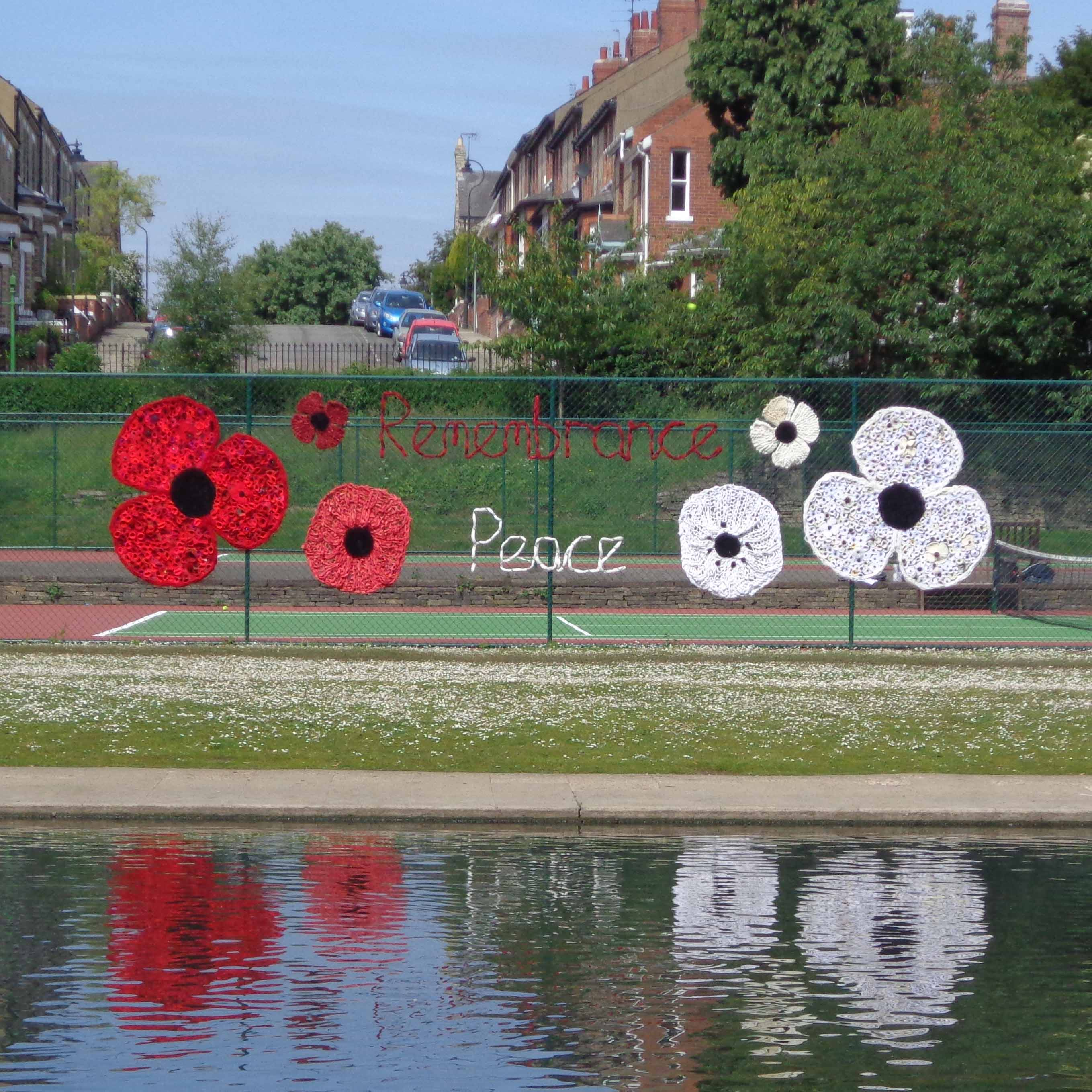 large red and white textile poppies displayed on a chain-link fence