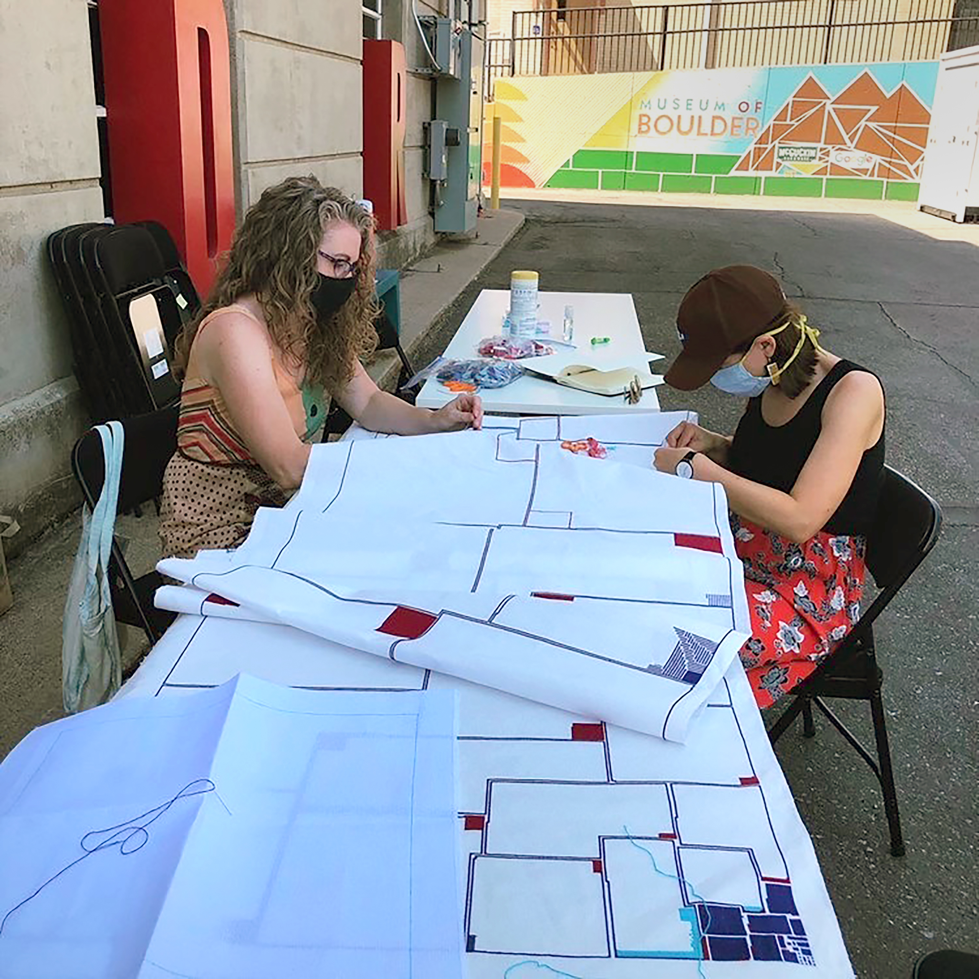 Two people sitting at on outdoor table, stitching on large cloths with geometric shapes.