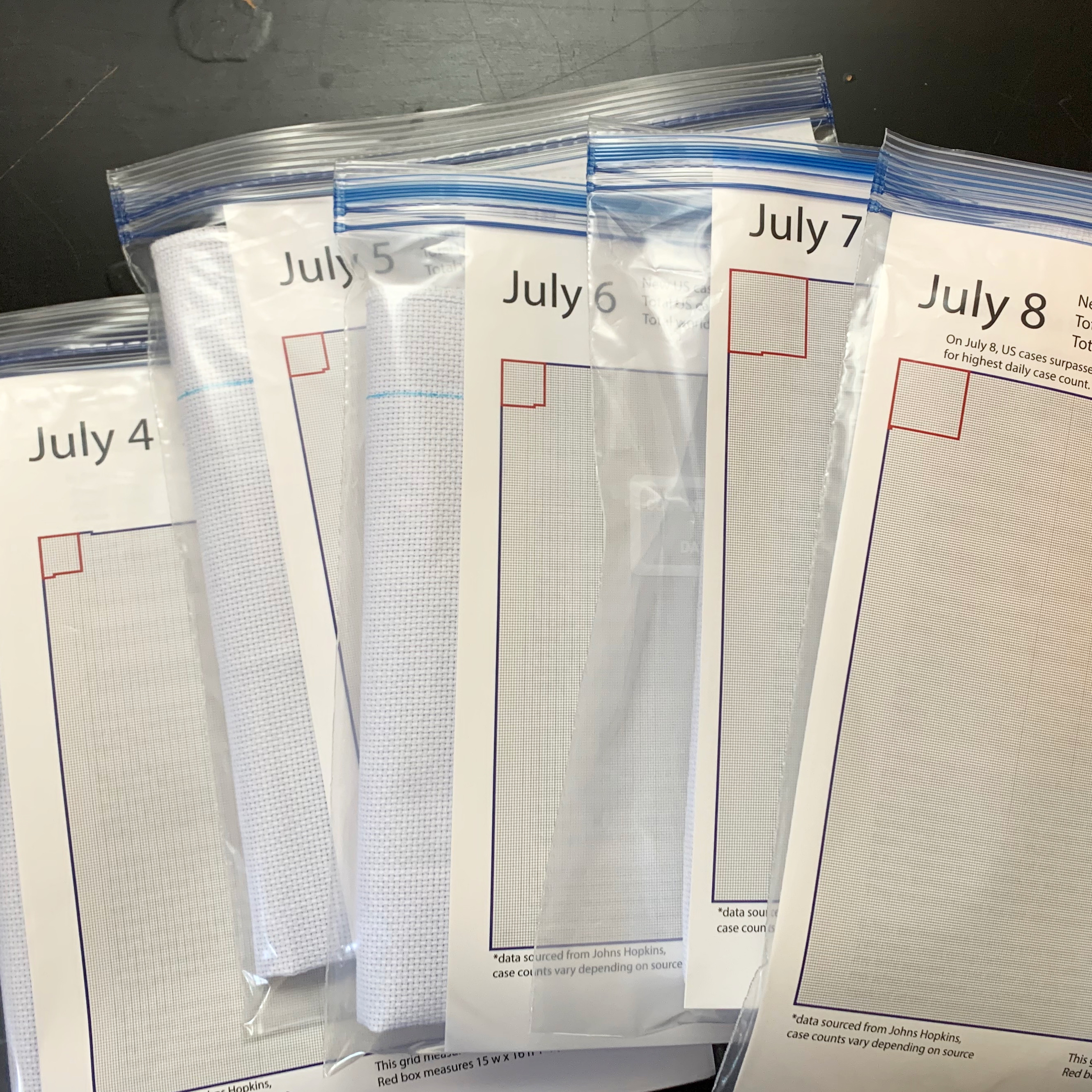 embroidery packs in plastic wallets, each with a different date in July.