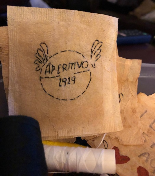 a close-up of an empty tea bag with 'Aperitivo 1919' stitched on to it in black thread